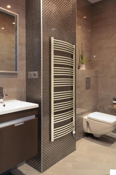 handtuchheizkörper Domi im Bad mit Fliesen an der Wand neben Spiegel