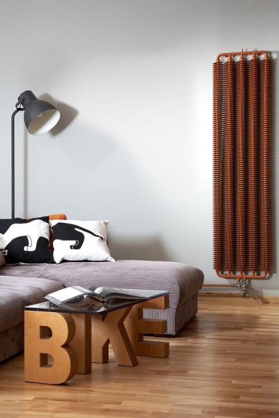 Designheizkörper Ribbon V arrangiert mit Thermostatventil in Chrom frontal neben Sofa