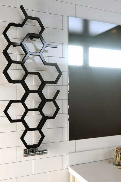 Design-Heizkörper HEX in schwarz an der Wand neben einem Spiegel