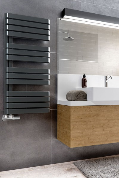 schwarzer Badheizkörper im Bedezimmer an der Wand neben einem Spiegel